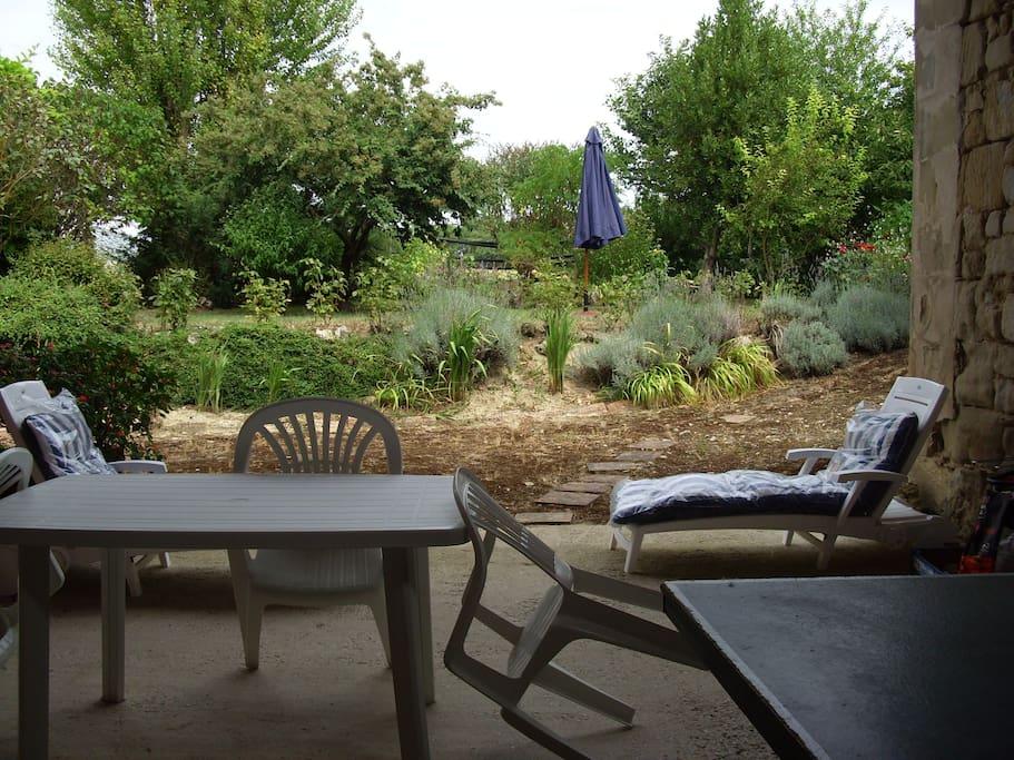 terrasse couverte qui donne sur un jardin et sur les champs
