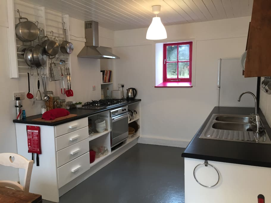 The kitchen with double sink, large fridge freezer, gas hob, extractor fan, electric oven, toaster, kettle, tea pots, cafetieres & espresso maker and well stocked with cooking untensils