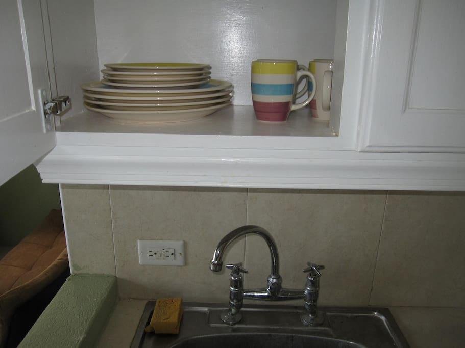 Dinnerware in cupboard above sink