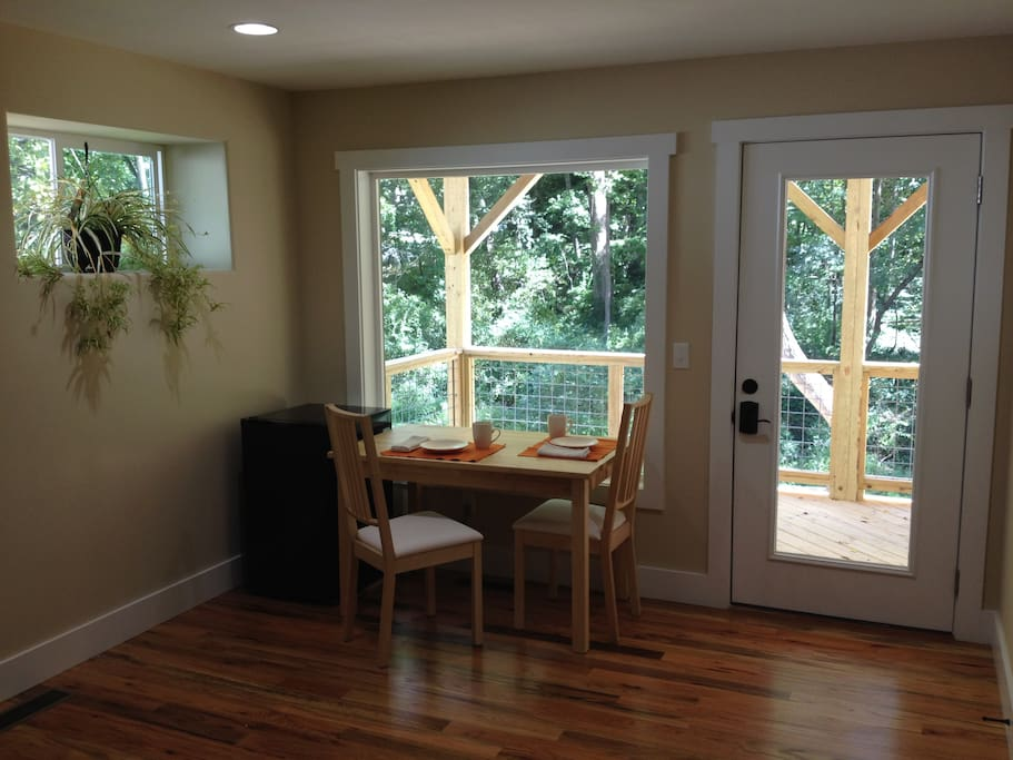 Breakfast nook with creek views, hardwood floors throughout and plenty of natural light