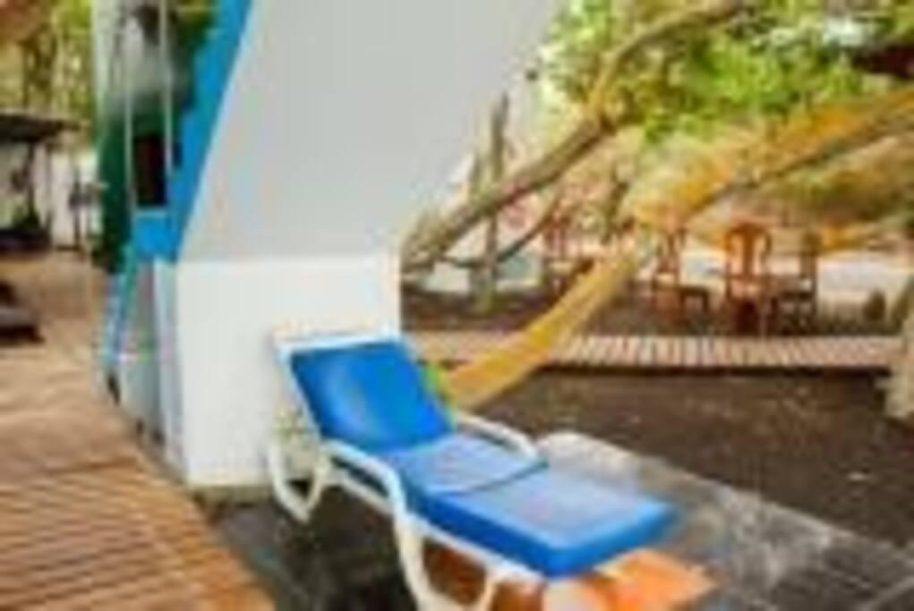 Cómoda tumbona, y mesas en el parea del jardín.