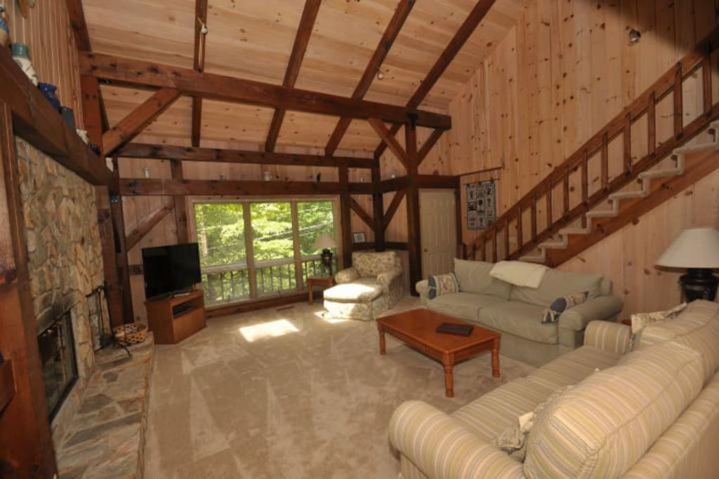 Large windows let natural light illuminate the wood and stone accents in this amazing log cabin.