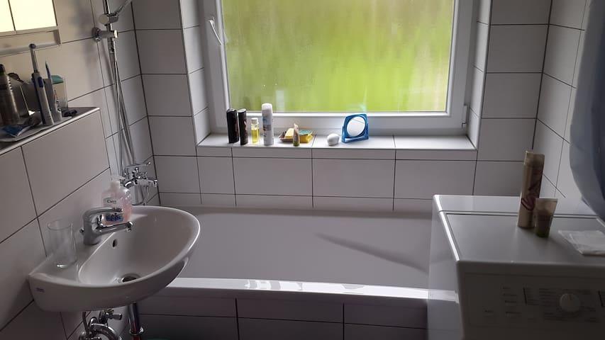 Badezimmer mit Badewann und Dusche/Regendusche, sowie Waschmaschine