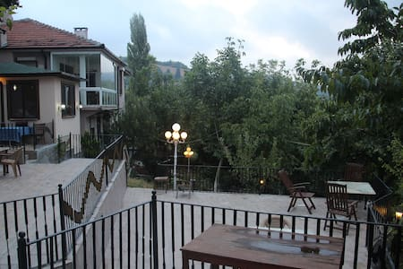 The villa is located on the slope of the mountain, above the village Yigitali. It has open green area with a winter garden with a full city view. It is 15 minutes from the city center.  You are invited to this natural, fruity and private experience.