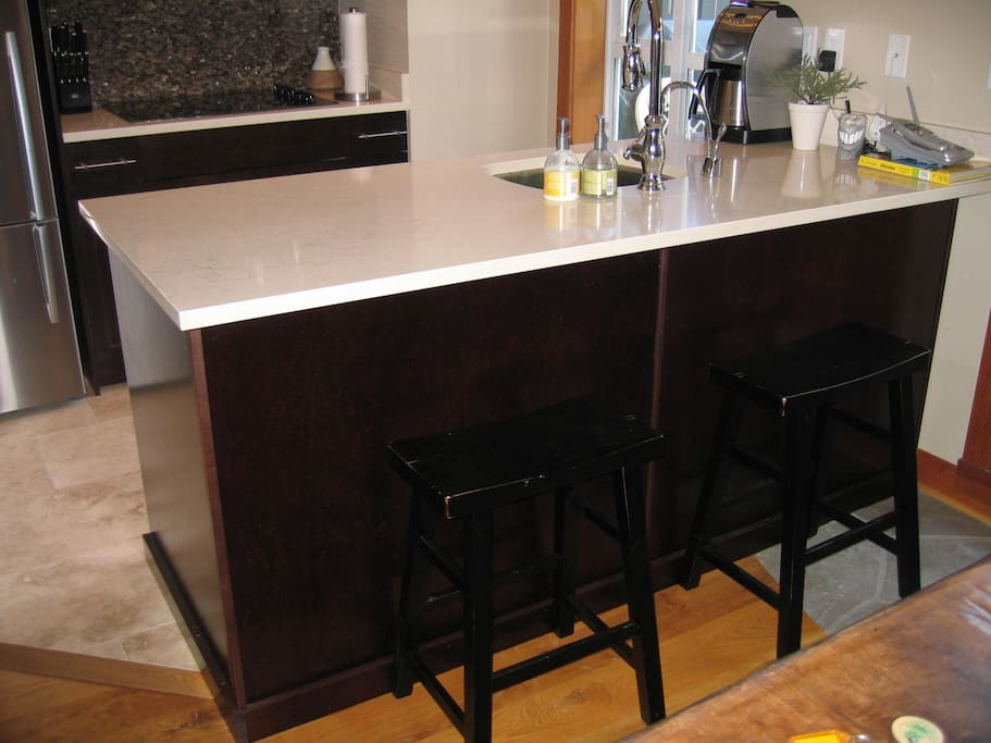 limestone counter tops & bar stools, lots of space to cook