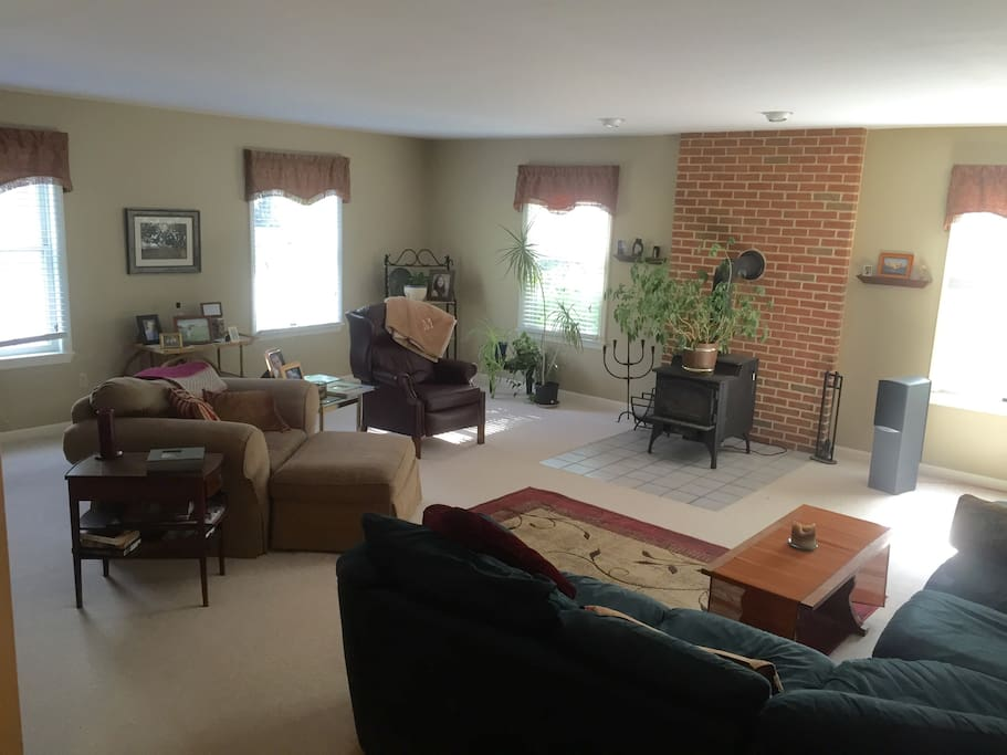 Large comfortable living room features luxurious wrap-around couch, leather recliner, stereo with Bose speakers, and flat screen TV