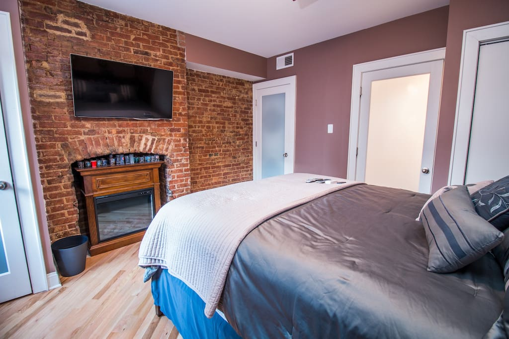 """Master bedroom with 40"""" Smart TV and electric fireplace/space heater"""