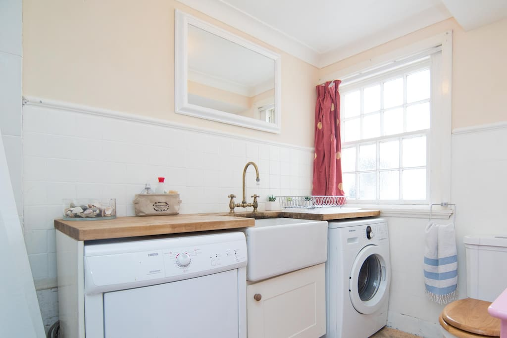 Utility shower-room with washing machine, condensing tumble dryer and Belfast sink.