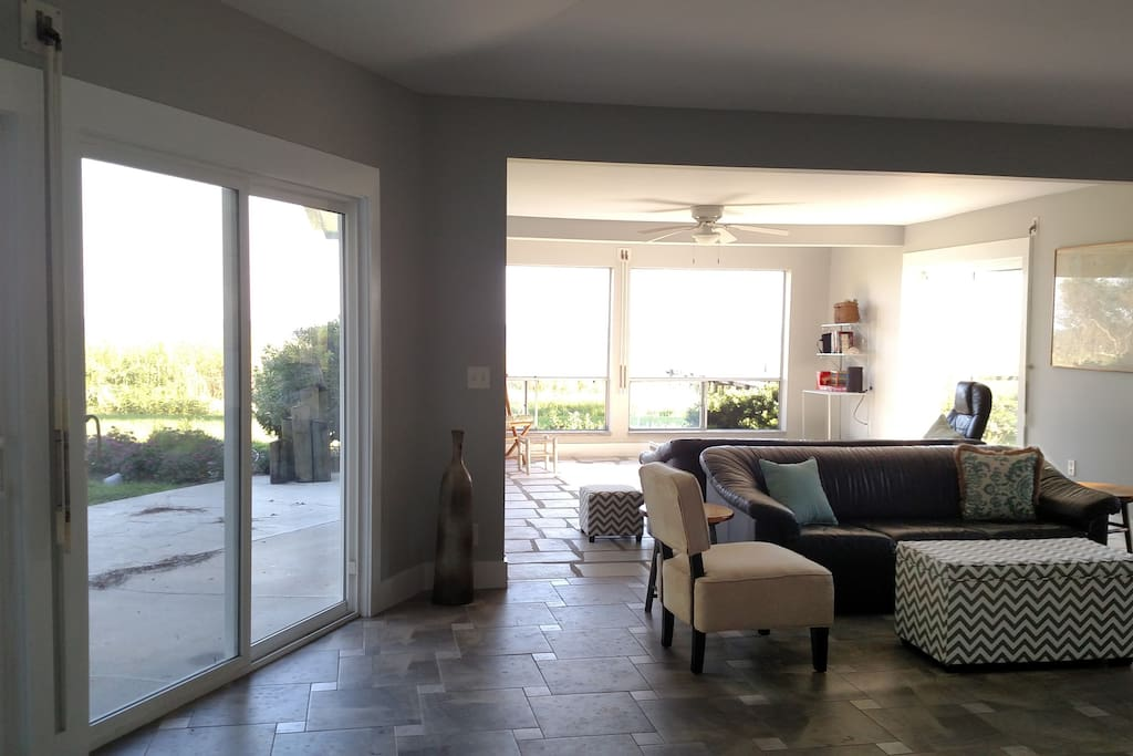 Sunlight floods the living area where back-to-back leather sofas offer views of the water or a fire in the fireplace.
