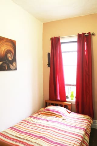 The Sunset bedroom has a full size bed, a small closet space and a large window facing the street.