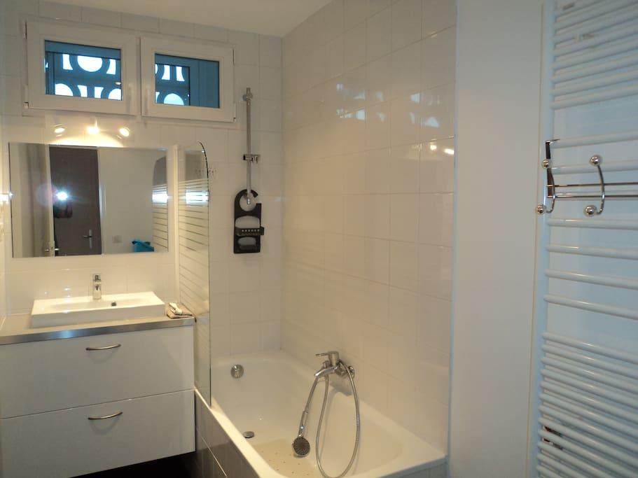 Salle de bains avec baignoire, lave-linge et sèche linge, toilettes séparées