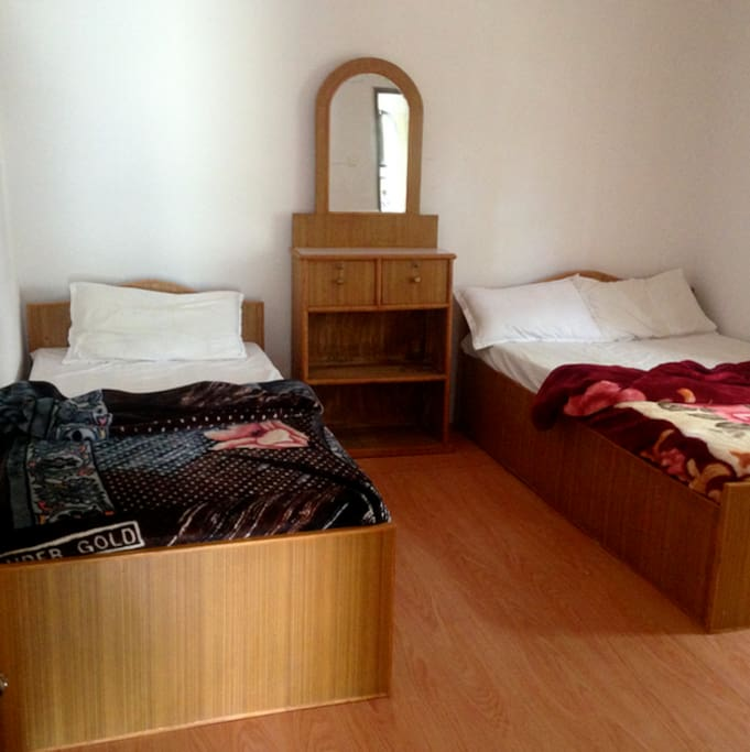 Each bed is made up with sheets and blankets.