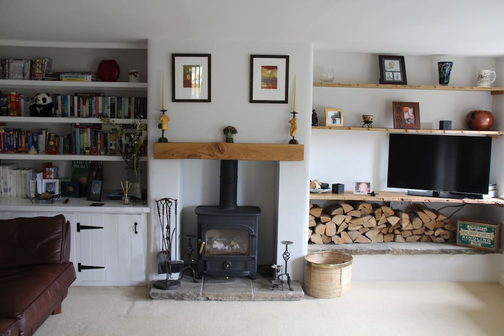 Lounge with log burner, and personal touches including books and boardgames
