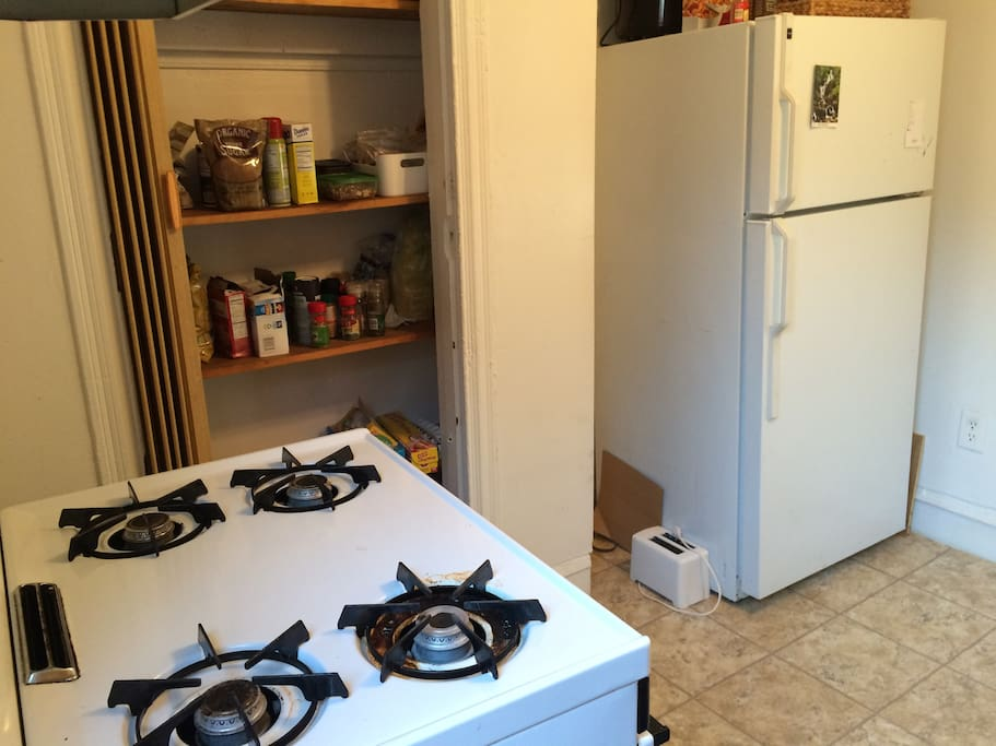 Kitchen with stoves, fridge, cabinet space and a fan.
