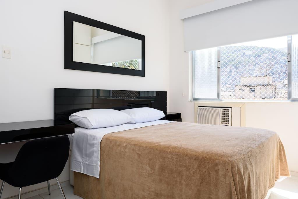 cama de casal, espelho e mesinhas de cabeceira