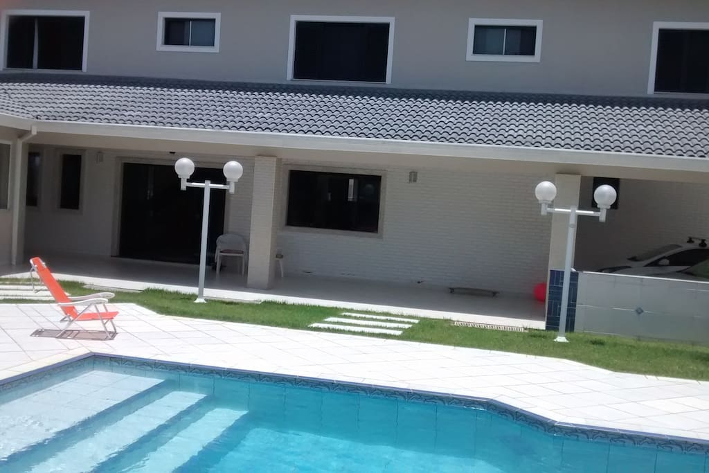 Vista parcial da piscina com a varanda lateral da casa.