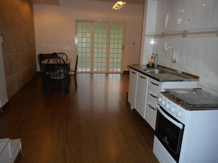 cozinha completa e sala de estar compartilhadas entre dois quartos