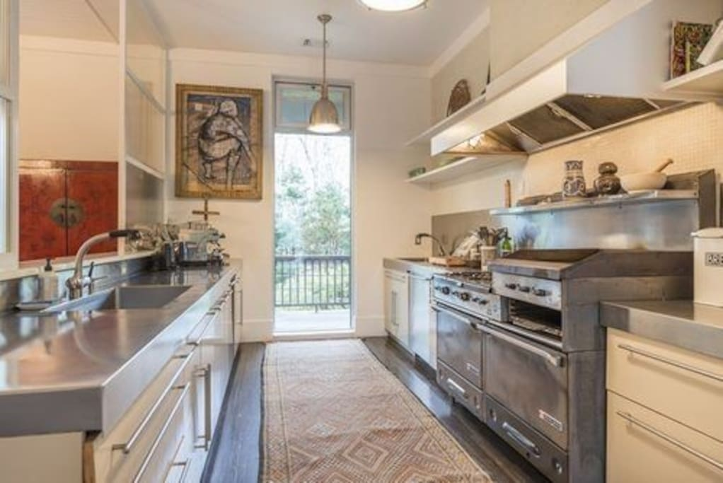 Spacious kitchen with 2 dishwashers, 2 sinks, Garland stove with 2 ovens, 6 burners, flat top and grill, and full wine fridge