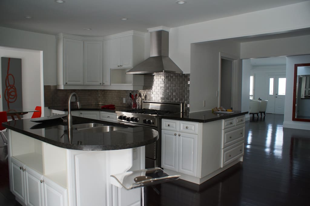 Gourmet Kitchen with gas stove/oven plus 2 electric ovens stools to sit around bar and a small tv.