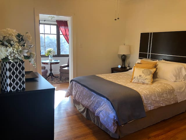 Roomy master bedroom with ceiling fan and attached private sunroom