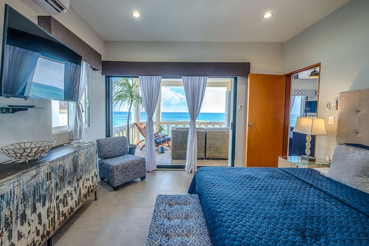 Master bedroom, with full wall sliding glass door, ottoman, cabinet space, and smart tv with Netflix.
