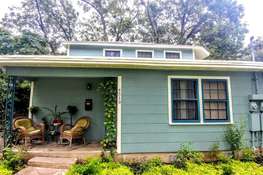 The house is nestled among a canopy of mature pecan trees.