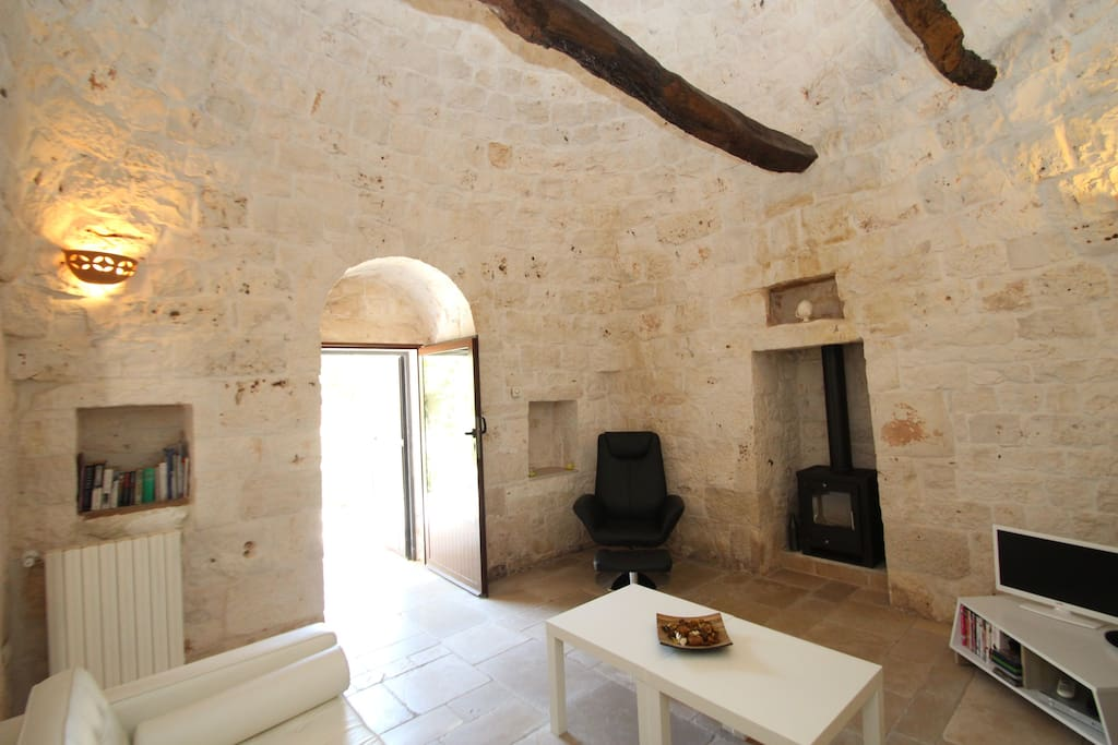 Trullo lounge with high ceilings and beams