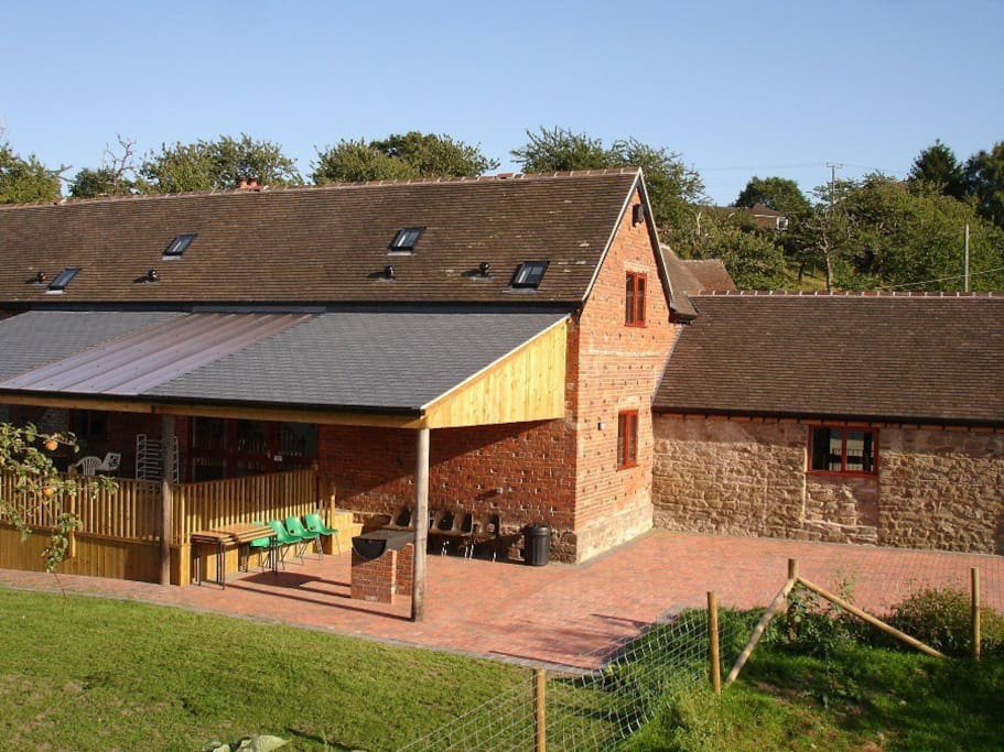External view of Barbecue area, lawn and covered decking - and sleeping barn.