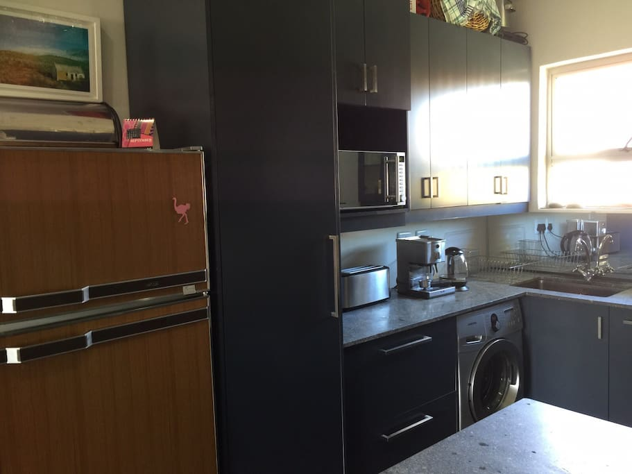 This is the kitchen. We have a washing machine, microwave and a refrigerator. We also have a dishwasher, stove and oven.