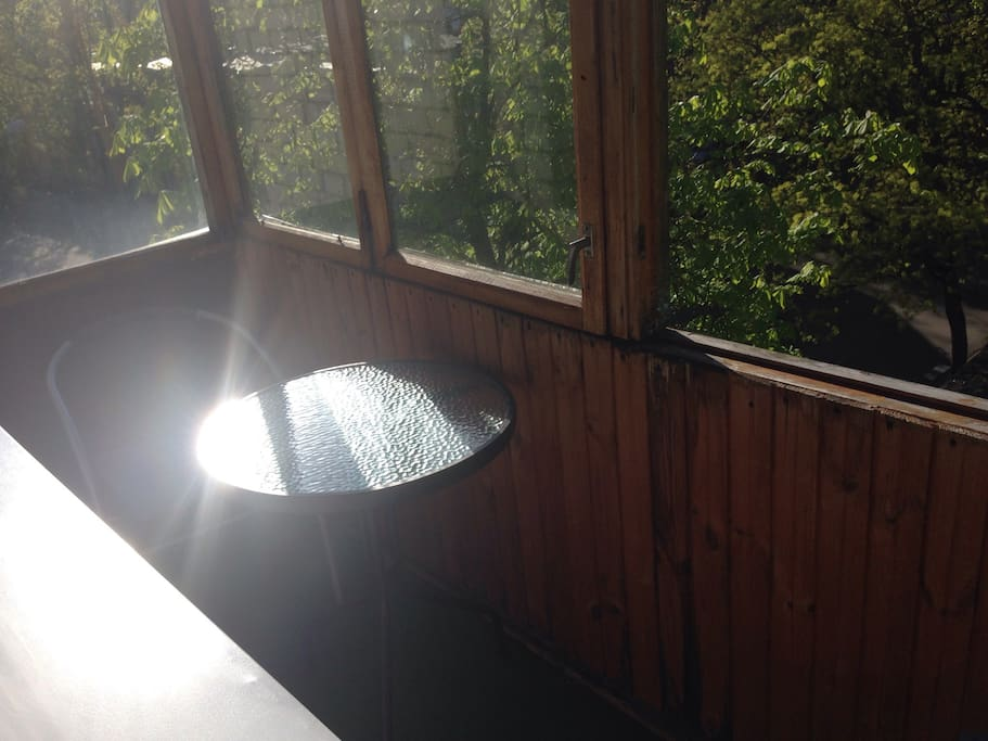 Застекленный балкон с столом и двумя креслами.