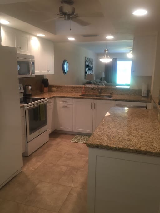 Newly renovated kitchen with solid surface countertops and new kitchen cabinets