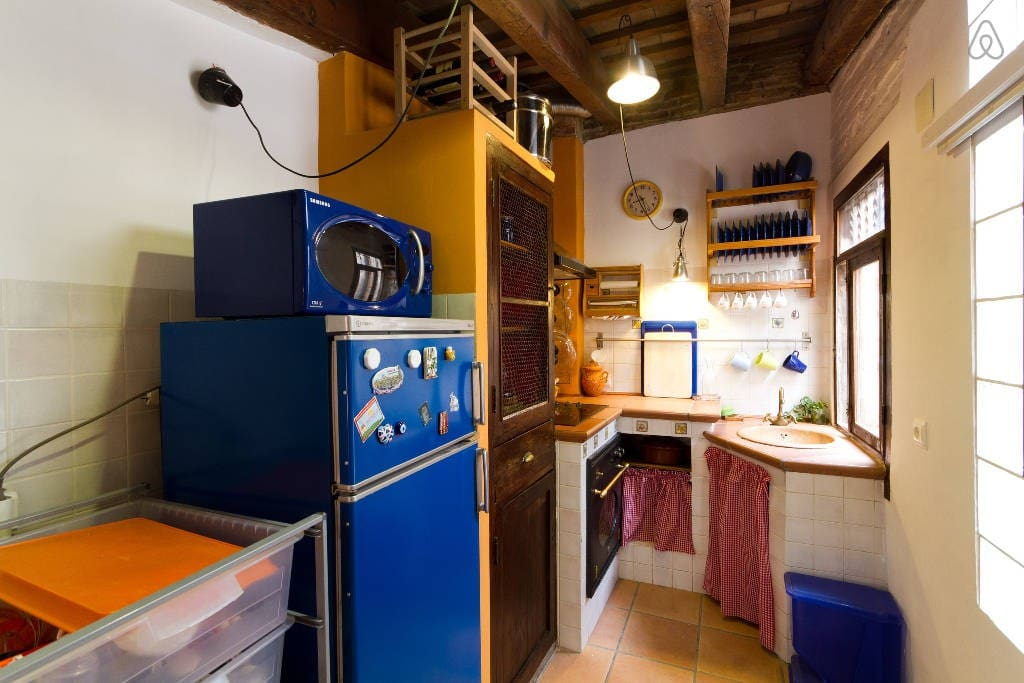 The kitchen has fridge, stove, toaster, microwave, and plates, glasses and cooking utensils.