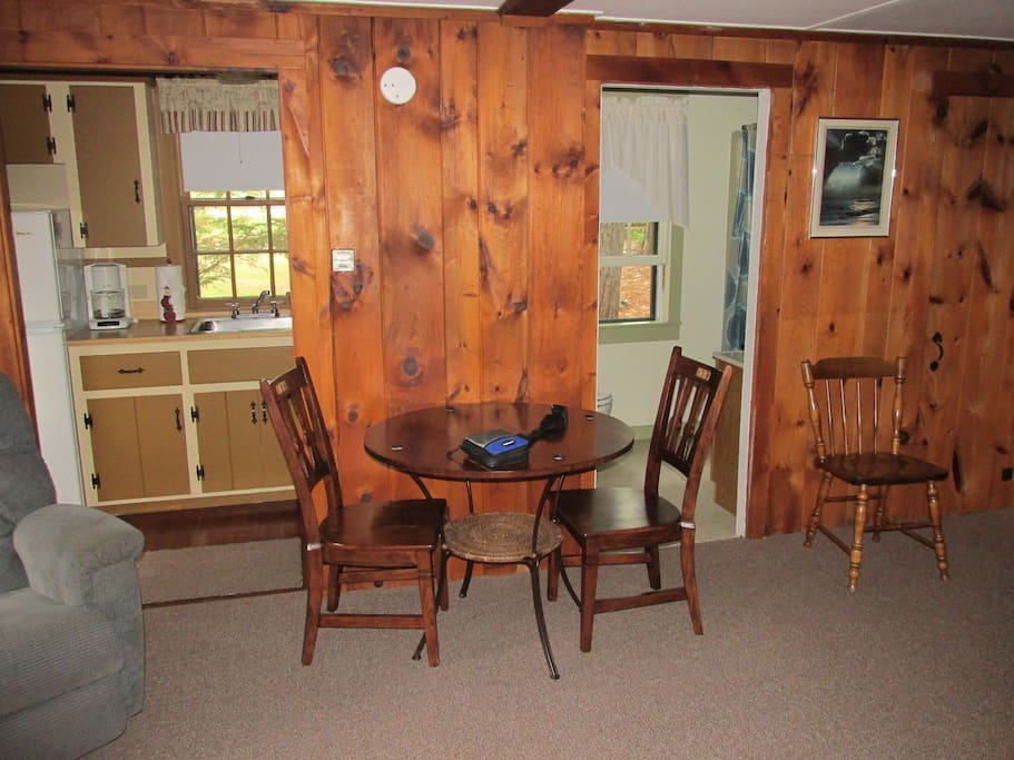 Kitchen (L), small table in living room, bathroom (R).