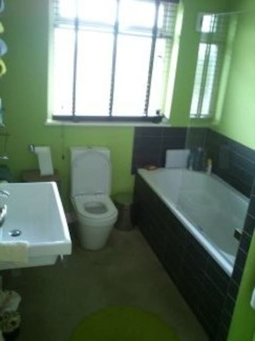 Bathroom has shower over bath sink and toilet plus a towel rail.