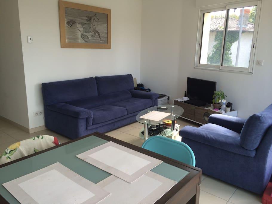 Coin salon avec canapé lit 2 places et accès direct sur la terrasse