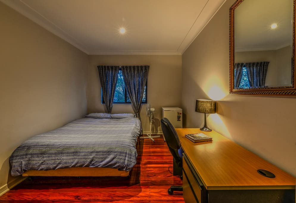 Large, spacious private room with comfortable bed, desk and appliances including private fridge and fan.