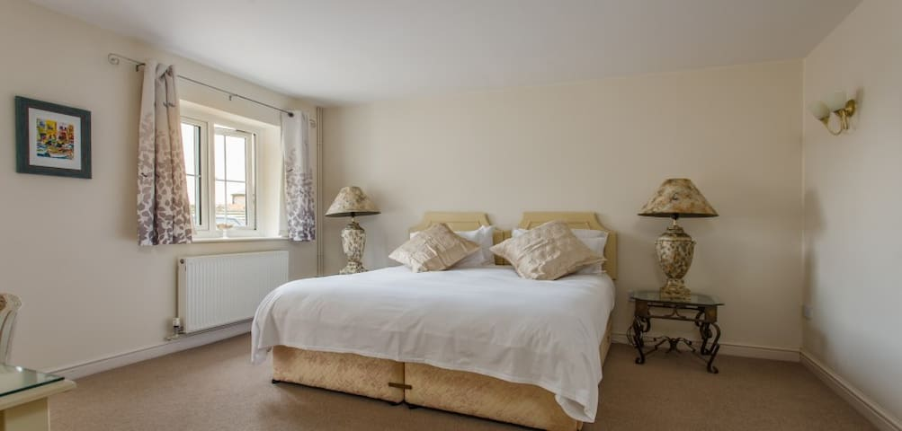Dairy Cottage Large Bedroom with 6ft wide King sized bed that can be split into two 3ft separate beds. Ensuite bathroom and walk in closet