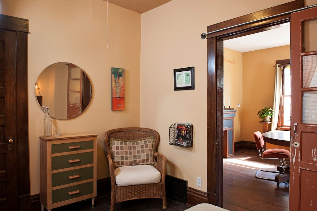 At the end of the bed sits a chair. The  chest of drawers & closet can be used for your belongings.