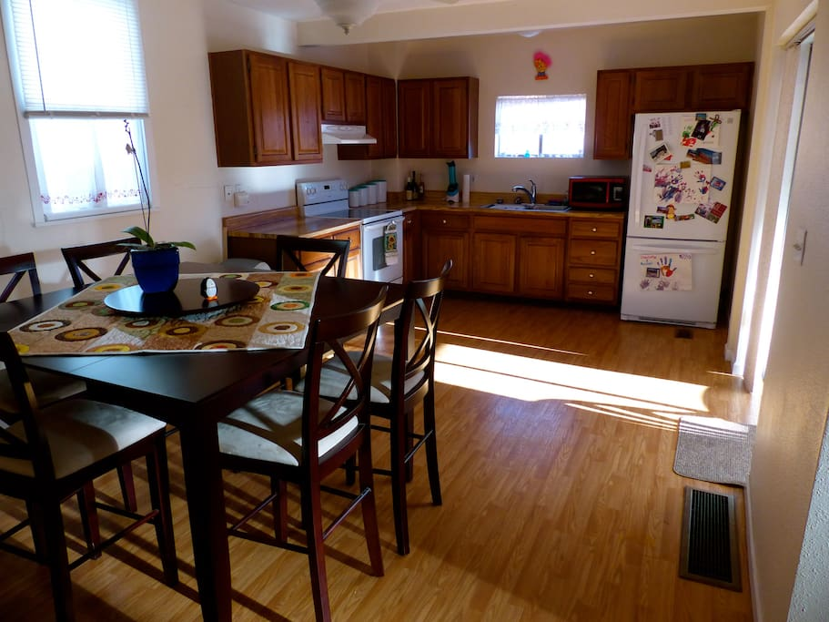Dining Room and Kitchen with door to the backyard which has a small grill for cooking and table for four