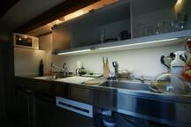 La cuisine luxe (Bulthaup) comprend 2 lave-vaissells (in/out, l'un faisant office de rangement l'autre accueillant la nouvelle vaisselle sale), il y a une platine de cuisson à induction (souris de commande inox cylindrique plate dans le tiroir inox), un four semi-pro à air chaud et un frigo désodorisé. La ventilation de la cuisine s'active contre le mur. Eclairages diodes et halogènes.