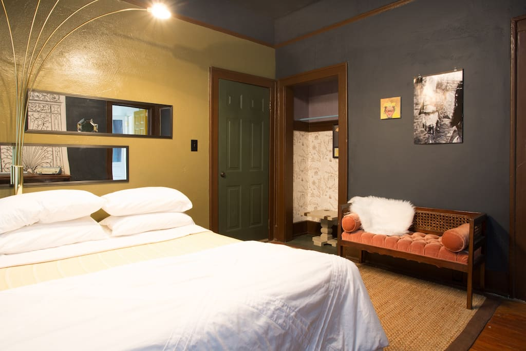 The bedroom features a queen sized bed with plenty of room to spread out and  rotating gallery wall of orginal local artwork and prints.