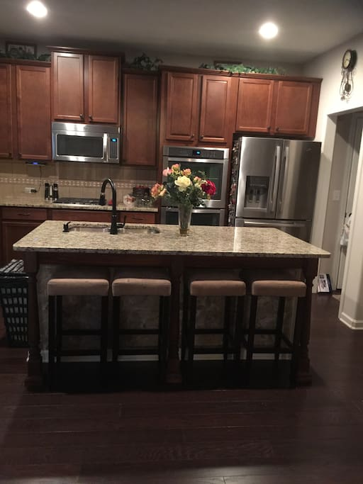 Granite breakfast bar, double stainless steel oven, French Doors stainless steel refrigerator, microwave.