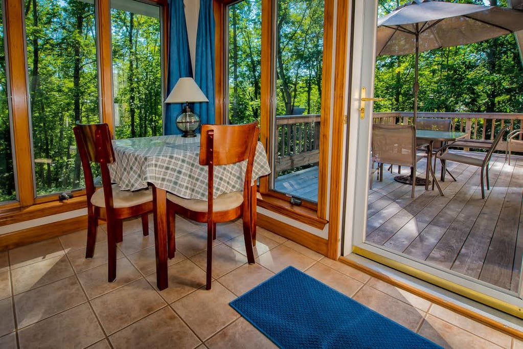 Table and chairs, access to the deck and outdoor seating.