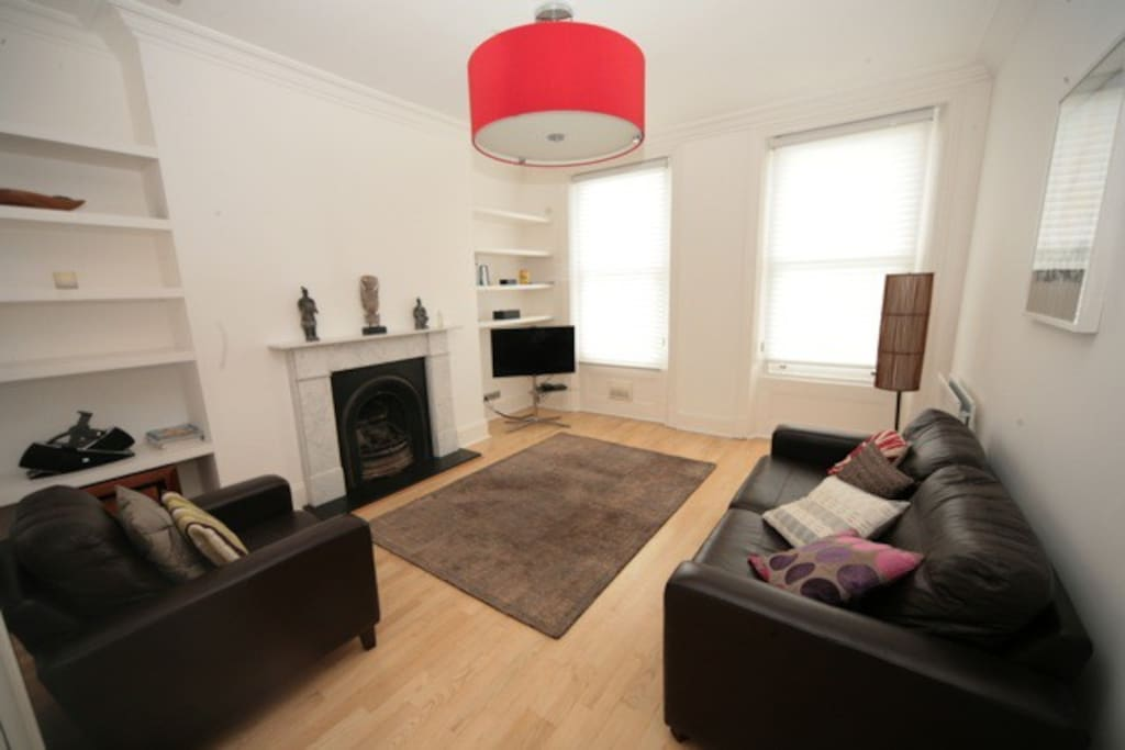 Living room with large hanging red light, fireplace (disabled) and sash windows with a view of Centre Court.  Wifi connected Samsung TV