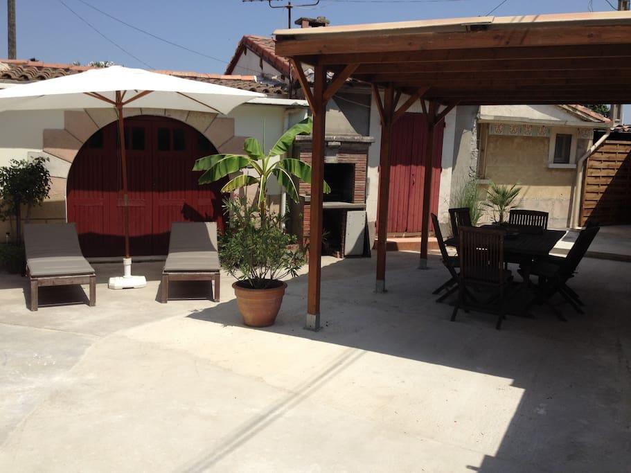 Cour fermée avec barbecue, bains de soleil, salon de jardin et jacuzzi.