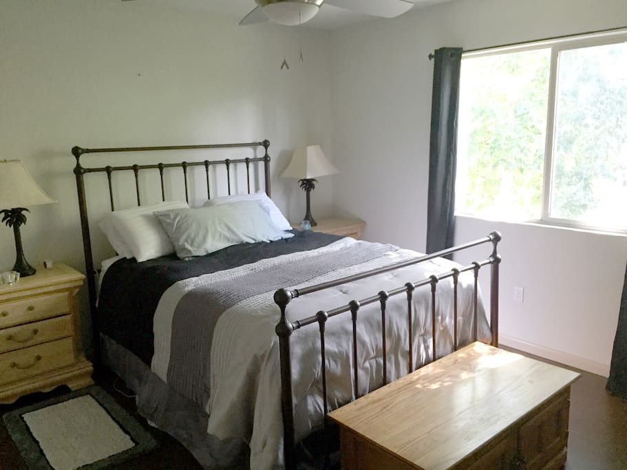 Master bedroom with queen bed. Room also includes a floor fan, overhead fan, black out curtains and a TV.
