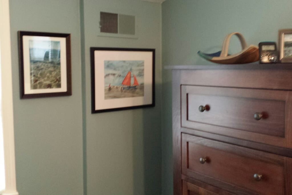 Family artwork and a large dresser in guest room