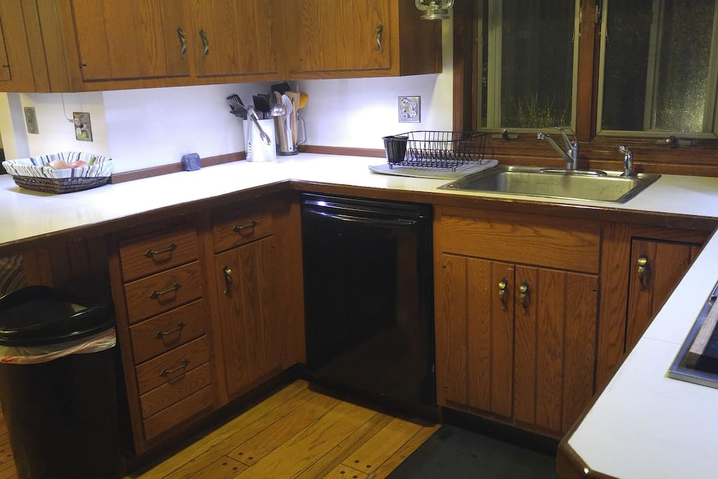 Kitchen with disposal, dishwasher, cooktop, stove, microwave, and oven.