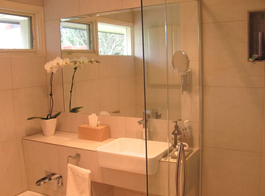 The brand new bathroom features a bath and walk-in shower, with rain effect