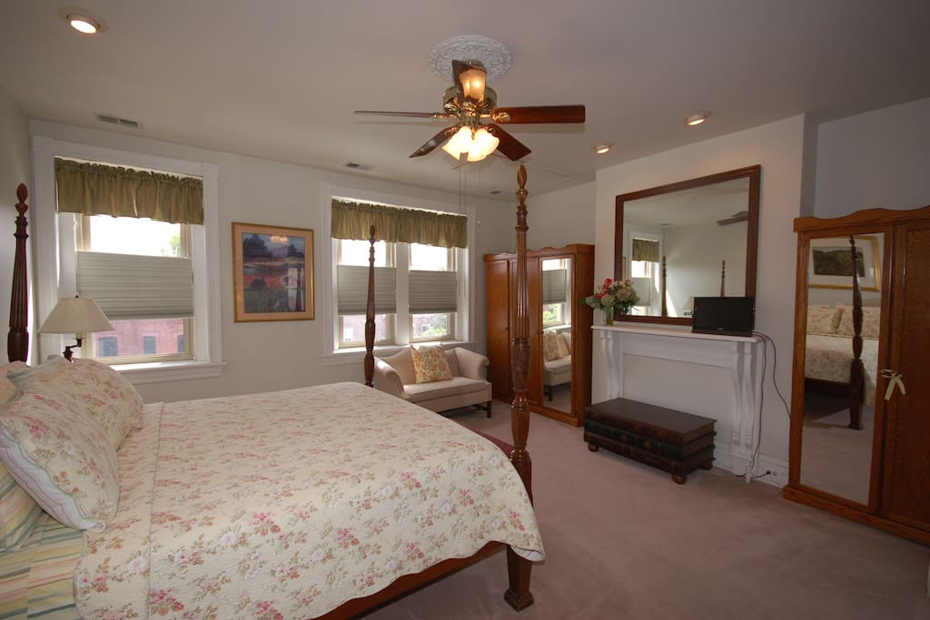 The room is furnished with a king size bed, desk, and attached private bath